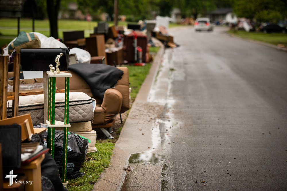 Damaged personal belongings from weekend flooding are set out on a residential street in Neosho, Mo., on Wednesday, May 3, 2017. LCMS Communications/Erik M. Lunsford