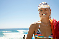 Woman in sun visor at beach head and shoulders