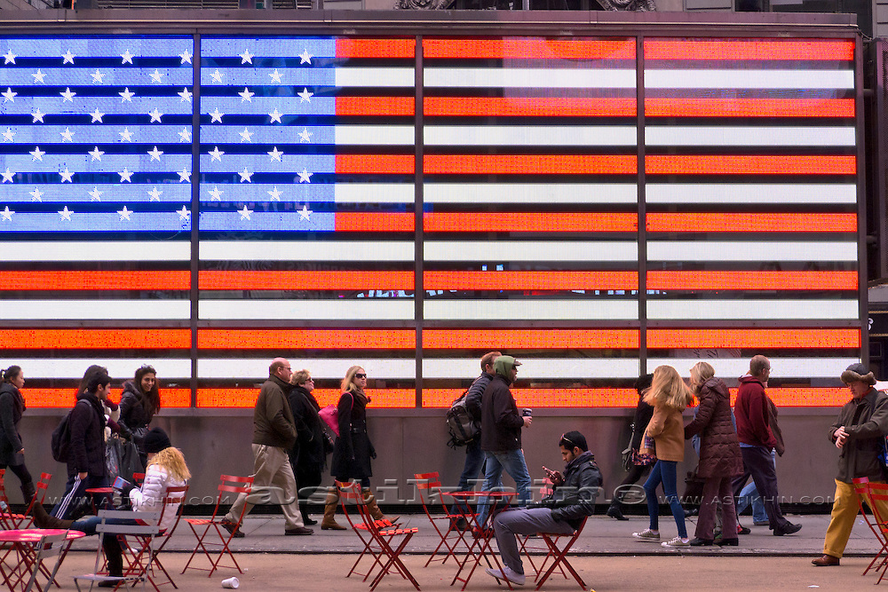 Silhouettes of People on the street in front of an American Flag.
