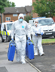 © London News Pictures. 29/07/2013. Manchester, UK. Police forensics officers outside a property on  Delta Walk, in Moston, Manchester where A father has been stabbed to death and his 13-year-old child left in a critical condition. A second man, who also suffered stab wounds,  died after he crashed a hijacked car into a nearby pub. Photo credit Steve Allen/LNP