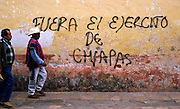 "FEB 24, 2001 - SAN CRISTOBAL DE LAS CASAS, CHIAPAS, MEXICO: Men walk past anti-government graffiti which says ""Army out of Chiapas"" on the wall of a church in San Cristobal de las Casas, Chiapas, Mexico, Feb. 25, 2001. Chiapas is the home of the EZLN, the Zapatistas who have been fighting a low level guerilla war against the government since January, 1994. San Cristobal is the intellectual center of the Zapatista movement and anti-government sentiment is strong in the southern Mexico city.  © Jack Kurtz   INDIGENOUS   POVERTY  WAR  VIOLENCE  HUMAN RIGHTS  CIVIL RIGHTS"
