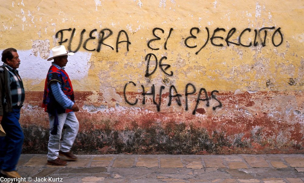 """FEB 24, 2001 - SAN CRISTOBAL DE LAS CASAS, CHIAPAS, MEXICO: Men walk past anti-government graffiti which says """"Army out of Chiapas"""" on the wall of a church in San Cristobal de las Casas, Chiapas, Mexico, Feb. 25, 2001. Chiapas is the home of the EZLN, the Zapatistas who have been fighting a low level guerilla war against the government since January, 1994. San Cristobal is the intellectual center of the Zapatista movement and anti-government sentiment is strong in the southern Mexico city.  © Jack Kurtz   INDIGENOUS   POVERTY  WAR  VIOLENCE  HUMAN RIGHTS  CIVIL RIGHTS"""
