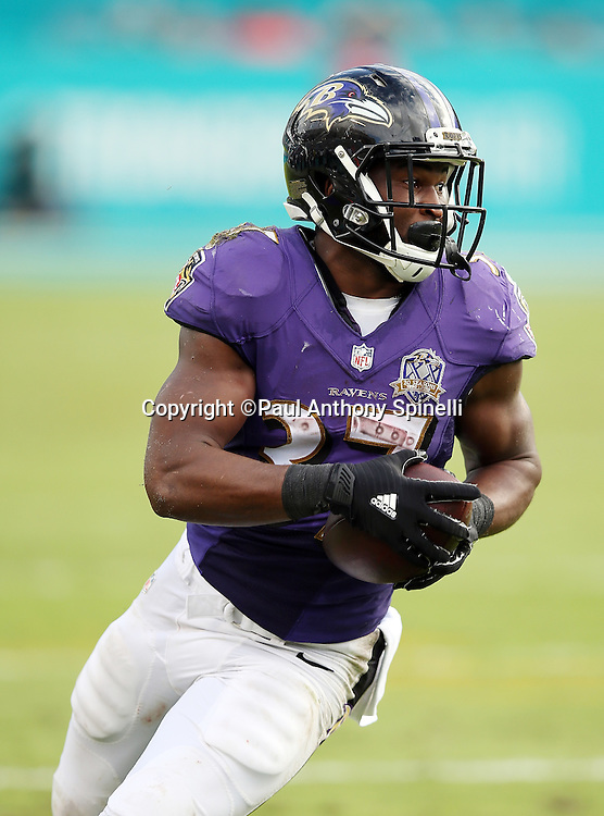 Baltimore Ravens running back Javorius Allen (37) looks for yardage as he catches a 41 yard touchdown pass that cuts the Miami Dolphins third quarter lead to 15-10 during the 2015 week 13 regular season NFL football game against the Miami Dolphins on Sunday, Dec. 6, 2015 in Miami Gardens, Fla. The Dolphins won the game 15-13. (©Paul Anthony Spinelli)