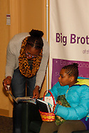 A little and big sister look at what came in an Easter basket at the Big Brothers Big Sisters of the Greater Miami Valley office in Moraine, Saturday, March 23, 2013.