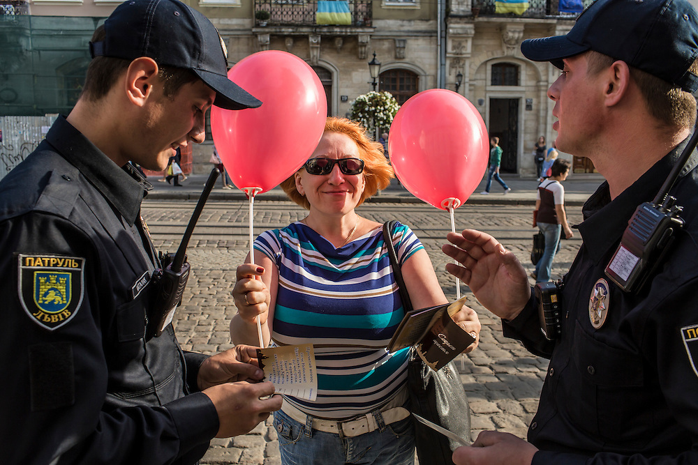 LVIV, UKRAINE - SEPTEMBER 15, 2015: Roman Katalakh, 22, and Vasil Spodayk, 33, right, both members of the new police, are offered balloons in Market Square, the tourist-friendly central square in Lviv, Ukraine. In an effort to reform the notoriously corrupt Ukrainian police force, an entirely new force has been established in several cities, including Kiev and Lviv, with a primary focus on patrolling the streets. CREDIT: Brendan Hoffman for The New York Times