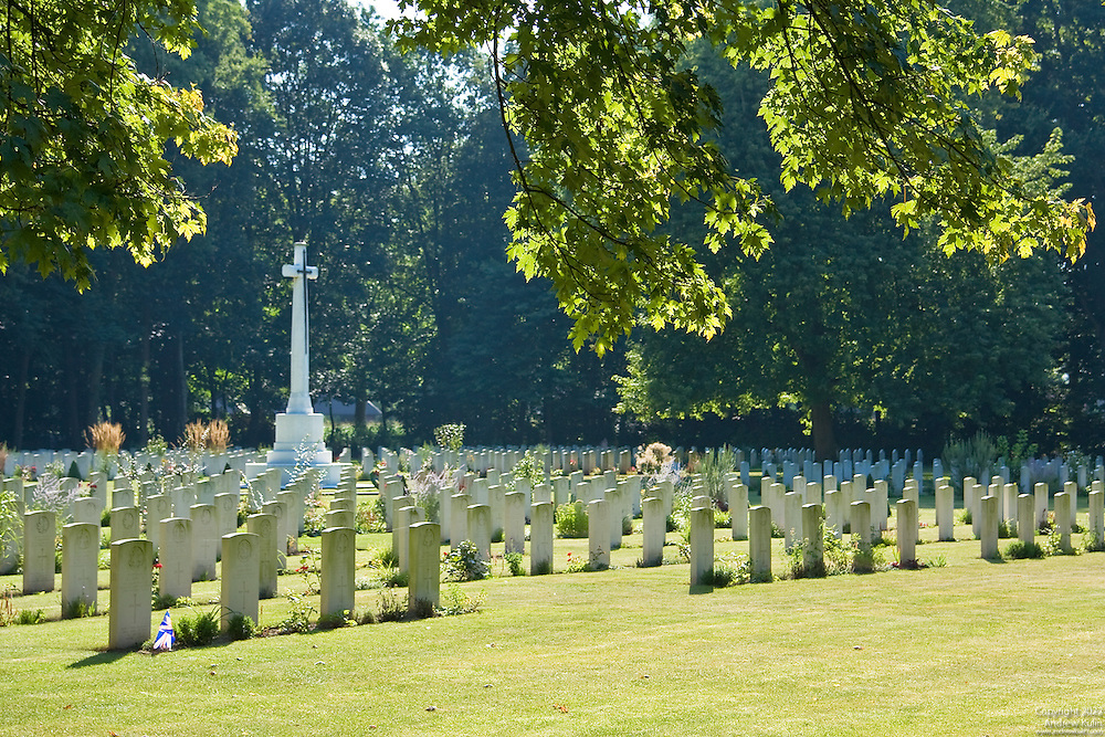 Headstones and Cross of Sacrifice framed by overhanging branches of a maple tree at the Adagem Canadian War Cemetary in Belgium.