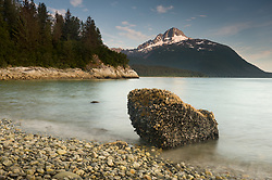 The rising tide envelopes a rock encrusted in blue mussels and acorn barnacles on a beach near the Klotz Hills and not far from Maquinna Cove in Muir Inlet in Glacier Bay National Park and Preserve in southeast Alaska. Prominent in the background is Mt. Wright which is located at the mouth of Adams Inlet. EDITORS NOTE: The use of a slow shutter speed smoothed the action of the waves.