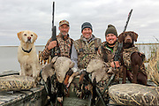 Successful waterfowl hunters (l-r) Keith Van Beusekom, Mike Brandriet, and Sam Brandriet, with their bag taken on Delta Marsh in Manitoba.