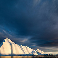 Greenland, Ilulissat, Midnight sun lights massive iceberg grounded near face of Jakobshavn Isfjord on stormy evening