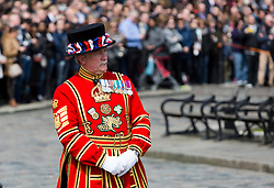 © Licensed to London News Pictures. 21/04/2016. London, UK. A Beefeater watches the Honourable Artillery Company (HAC) fire a 62 round gun salute at The Tower of London, near Tower Bridge to mark the 90th birthday of Great Britain's Queen Elizabeth II. A Royal Salute normally comprises 21 guns, but is increased to 41 if fired from a Royal Park or Residence and uniquely, at The Tower of London, a total of 62 rounds are fired on Royal anniversaries, including an additional 21 guns for the citizens of the City of London to show loyalty to the Monarch.  Photo credit : Vickie Flores/LNP