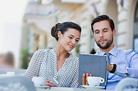 Businessman discussing plans over digital tablet to businesswoman while sitting and waiting for their food at restaurant