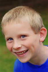 Portrait of young boy with autism smiling,