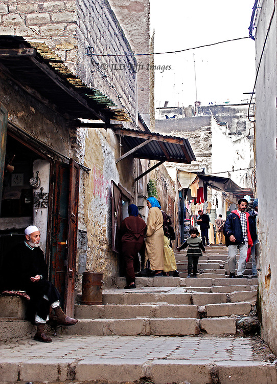 Stepped street in Fes, looking up the stairs.  Shopkeeper seated at left, women and children shopping a few steps up, young man in a jacket stepping down toward the camera, others at the top where clothing hangs for sale.