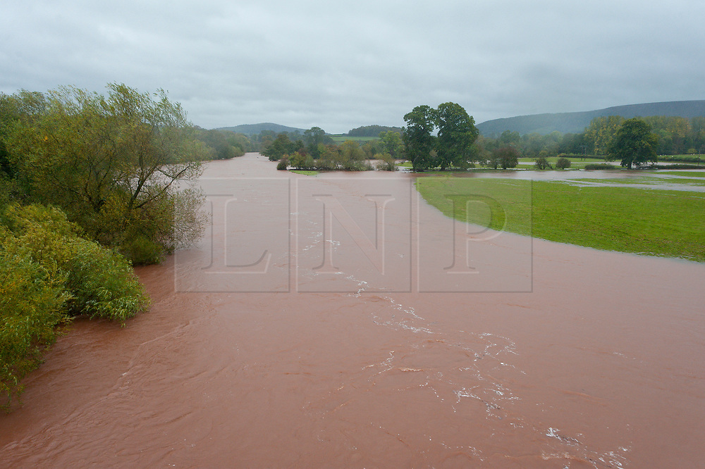 © Licensed to London News Pictures. 13/10/2018. Crickhowell, Powys, Wales, UK. The river Usk near Brecon in Powys. Fireservices pump out The Bridge End Inn, (landlord Howard Baker) at Crickhowell in Powys, Wales, UK.Storm Callum continues to devastate South Wales as the River Usk bursts it's banks as a result of  massive torrential rainfall in Powys flooding many riverside properties. Photo credit: Graham M. Lawrence/LNP