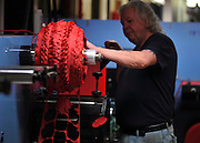 © Licensed to London News Pictures. 07/11/2011. Richmond, UK.  Terry Nutbeam, who has worked at the factory for 22 years, operates a machine that cuts the red petals for the poppies. Red Poppies being made in The Poppy Factory in preparation for sale in 2012, Richmond, Surrey today 7th November.  The factory has been supplying the poppy, crosses and wreathes to the British Legion for almost 90 years. It is staffed by veterans, many whom of which are injured, sick or wounded of all ages. Photo credit : Stephen Simpson/LNP