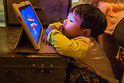 "25 JANUARY 2014 - BANG LUANG, NAKHON PATHOM, THAILAND: A child whose parents are opera performers plays with a tablet computer while his parents are on stage at a show in a Chinese shrine in the town of Bang Luang, Nakhon Pathom, Thailand. The Sing Tong Teochew opera troupe has been together for 60 years and travels through central Thailand and Bangkok performing for mostly ethnic Chinese audiences. Chinese opera was once very popular in Thailand, where it is called ""Ngiew."" It is usually performed in the Teochew language. Millions of Chinese emigrated to Thailand (then Siam) in the 18th and 19th centuries and brought their cultural practices with them. Recently the popularity of ngiew has faded as people turn to performances of opera on DVD or movies. There are still as many 30 Chinese opera troupes left in Bangkok and its environs. They are especially busy during Chinese New Year when travel from Chinese temple to Chinese temple performing on stages they put up in streets near the temple, sometimes sleeping on hammocks they sling under their stage.     PHOTO BY JACK KURTZ"