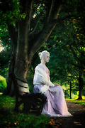 a woman in a pink dress with a white shawl is sitting on a bench in a park
