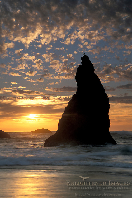 Clouds at sunset over jagged coastal rocks reflection in ocean waves breaking on Bandon State Beach, Oregon