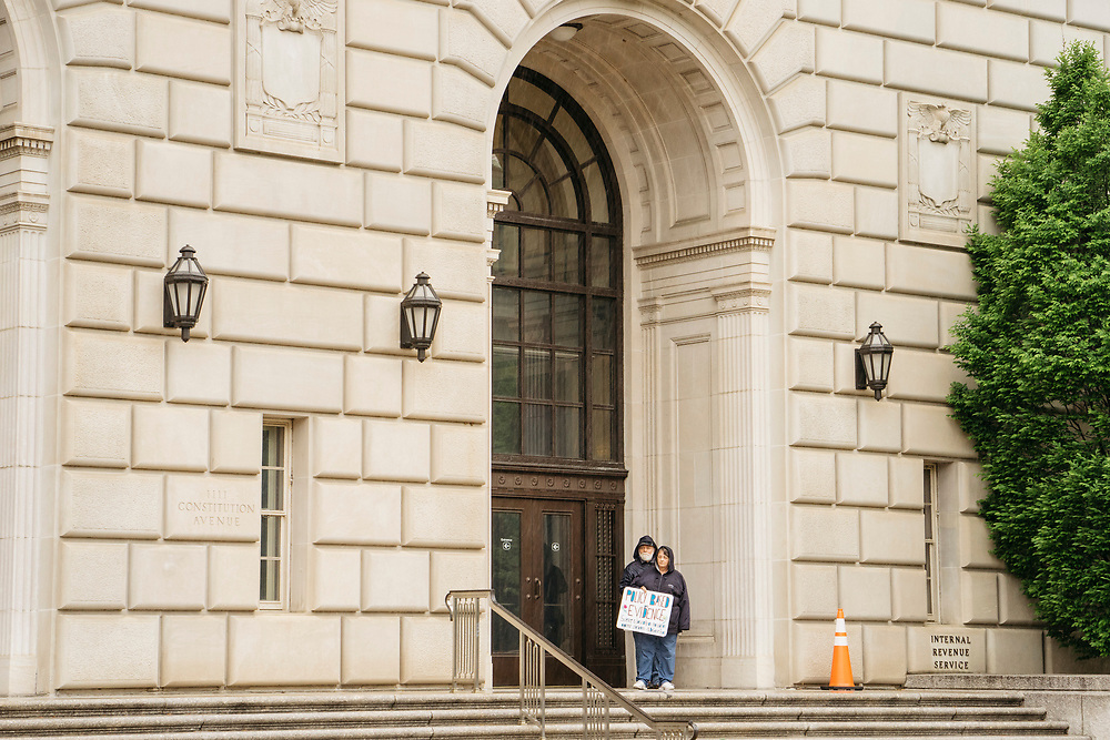 Protesters hold signs in the doorway of the IRS during the March for Science in Washington, D.C. on Earth Day 2017.
