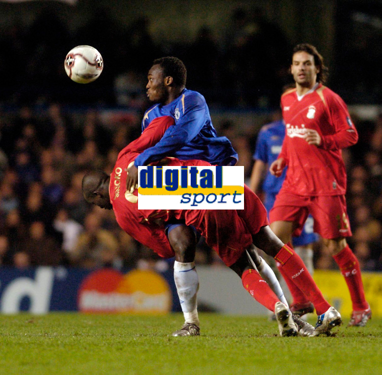 Photo: Leigh Quinnell.<br /> Chelsea v Liverpool. UEFA Champions League. <br /> 06/12/2005. Chelseas Michael Essien holds on to Liverpools Mohamed Sissoko while trying to head the ball.