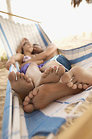 Couple Sleeping in Hammock on Beach