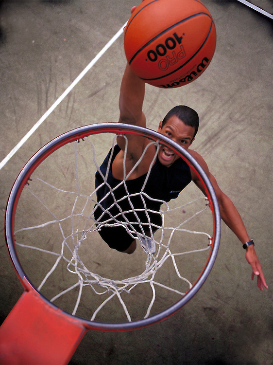 San Diego Fitness Photographer: Young basketball player makes a slam dunk on outside court in Los Angeles, CA. USA