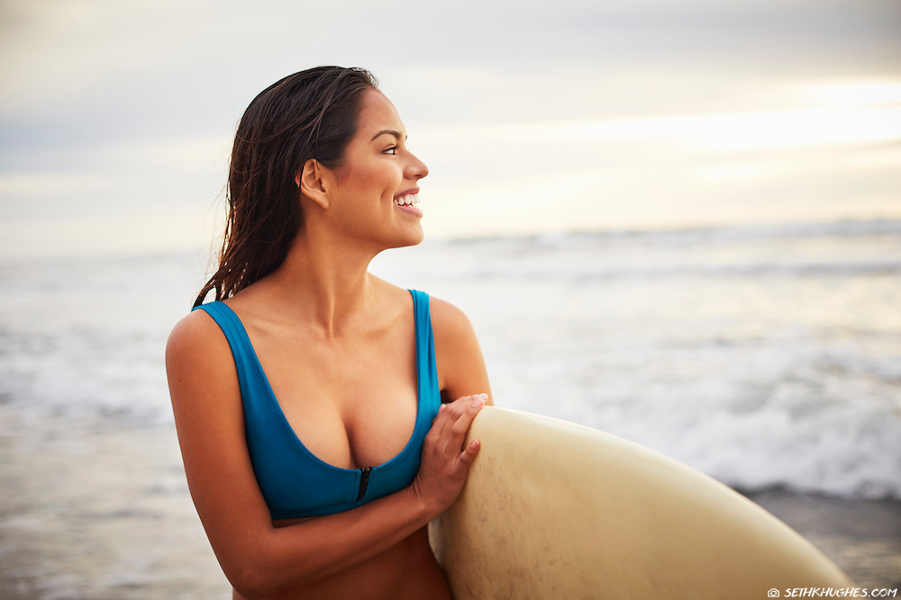 A beautiful young woman walks out of the surf smiling on the beach of San Diego, California.