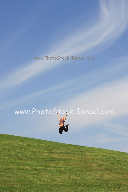 excited youg woman jumps on a knoll