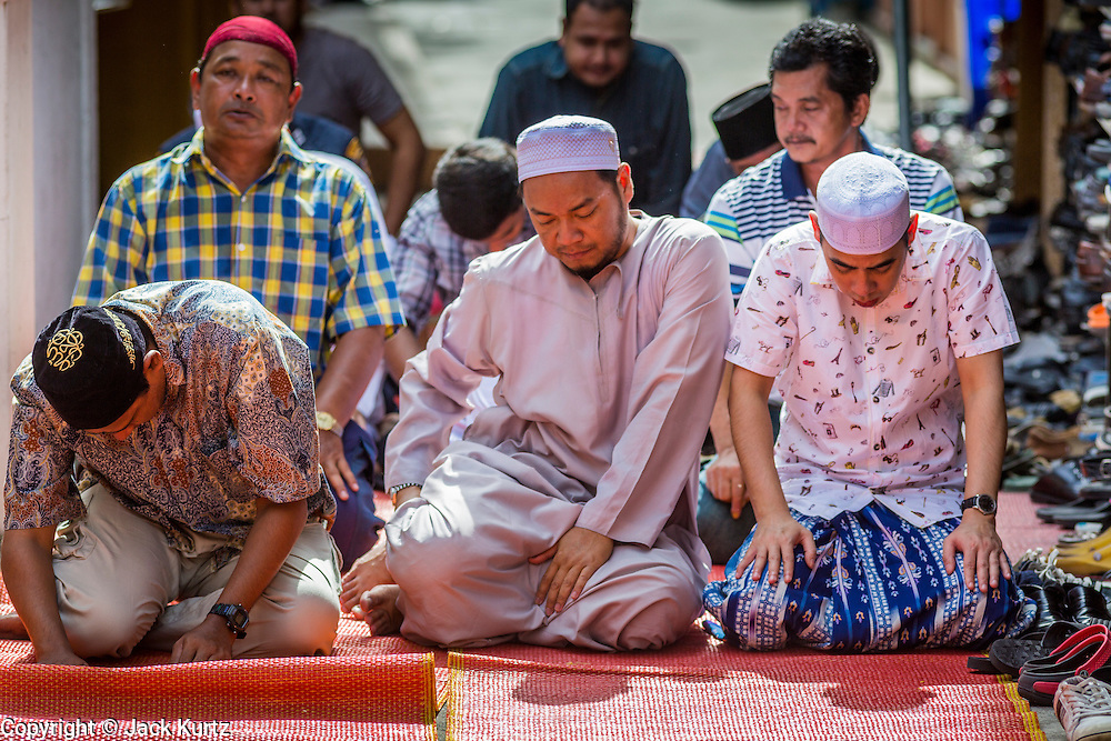 """08 AUGUST 2013 - BANGKOK, THAILAND: Men pray outside during Eid al-Fitr services at Haroon Mosque in Bangkok. Eid al-Fitr is the """"festival of breaking of the fast,"""" it's also called the Lesser Eid. It's an important religious holiday celebrated by Muslims worldwide that marks the end of Ramadan, the Islamic holy month of fasting. The religious Eid is a single day and Muslims are not permitted to fast that day. The holiday celebrates the conclusion of the 29 or 30 days of dawn-to-sunset fasting during the entire month of Ramadan. This is a day when Muslims around the world show a common goal of unity. The date for the start of any lunar Hijri month varies based on the observation of new moon by local religious authorities, so the exact day of celebration varies by locality.      PHOTO BY JACK KURTZ"""
