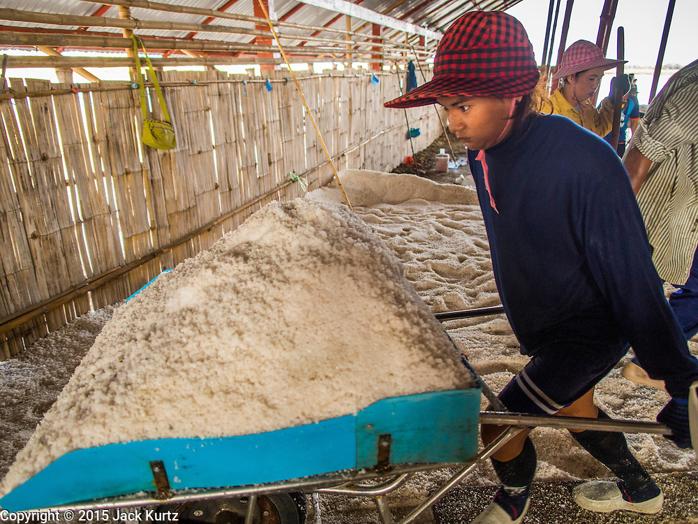09 MARCH 2015 - NA KHOK, SAMUT SAKHON, THAILAND: A Burmese migrant worker on a salt farm near Samut Sakhon, Thailand, brings salt to a warehouse during the salt harvest. The coastal provinces of Samut Sakhon and Samut Songkhram, about 60 miles from Bangkok, are the center of Thailand's sea salt industry. Salt farmers harvest salt from the waters of the Gulf of Siam by flooding fields and then letting them dry through evaporation, leaving a crust of salt behind. Salt is harvested through dry season, usually February to April. The 2014 salt harvest went well into May because the dry season lasted longer than normal. Last year's harvest resulted in a surplus of salt, driving prices down. Some warehouses are still storing salt from last year. It's been very dry so far this year and the 2015 harvest is running ahead of last year's bumper crop. One salt farmer said prices are down about 15 percent from last year.    PHOTO BY JACK KURTZ