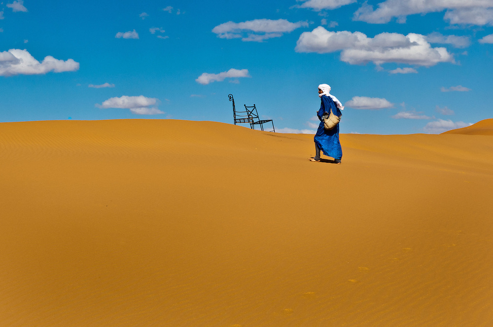 A Berber walks across the saharan dunes of the Erg Chebbi leaving chairs behind.