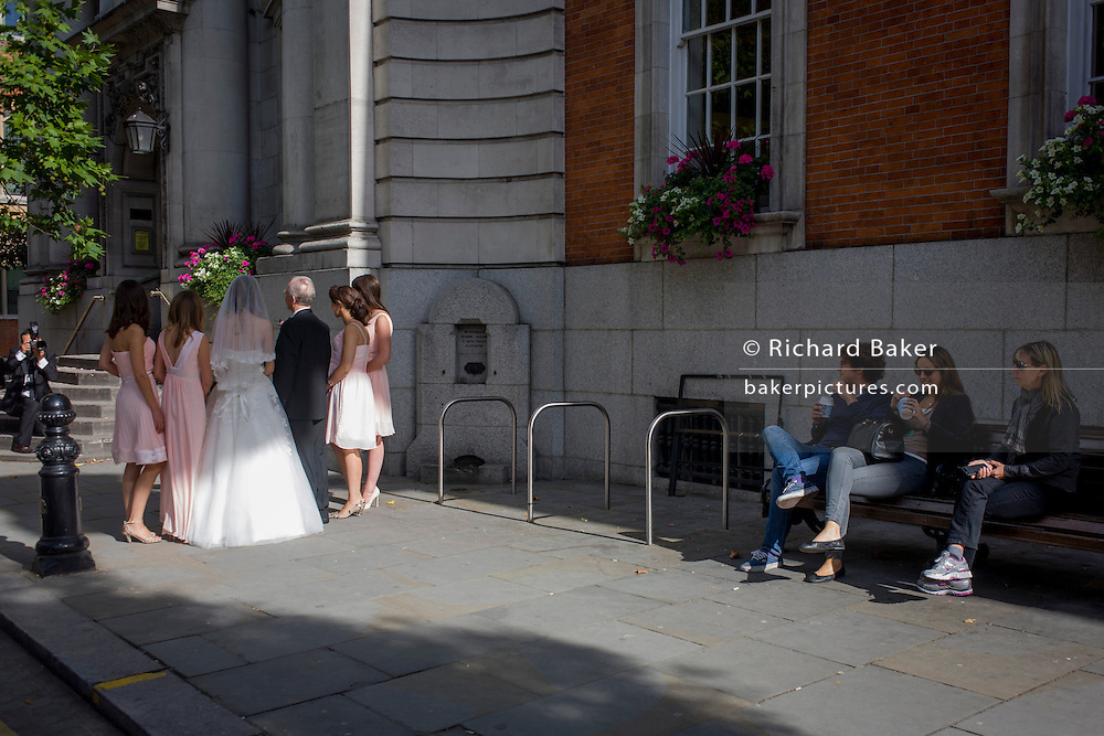 People watch a bride and bridesmaids from a civil wedding ceremony outside Chelsea Registry Office
