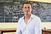 VSO volunteer Paul Jennings  sitting in front of a blackboard in one of the classrooms of Angaza school, Lindi, Tanzania