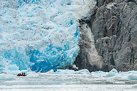 Small boat dwarfed by the face of South Sawyer Glacier in Tracy Arm - Fords Terror Wilderness in Southeast Alaska.