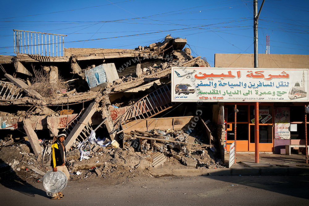A boy is walking by a building still showing signs of the 2004 US-led battles on the streets of Fallujah, Iraq.