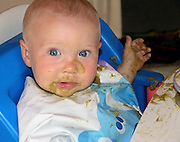 toddler boy with creamed spinach on face, hands, bib, high chair
