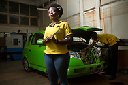 """Pauline Korukundo, 29, Vehicle Integration Manager at Kiira Motors Corporation, with the company's first vehicle at the workshop where it was created at Makerere University, in Kampala, Uganda. """"My vision for the company is to see cars made by us, so that we as Ugandans can begin to believe more in ourselves,"""" says Korukundo."""