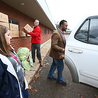 Blair Weaver, from left, Kevin Warren and Marcus Gary load boxes of food into waiting cars at the Baldwyn School District Food Pantry Thursday afternoon.