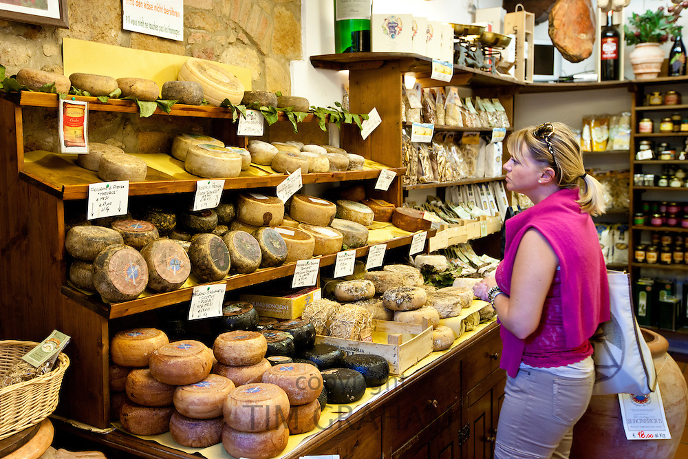 Shopper in Italian artisan cheese shop, Del Bottega Naturista selling Pecorino Stagionato aged cheese in Pienza, Tuscany, Italy