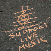 Chalk Street Art quote &quot; Support Live Music&quot; on the side walk in Washington Square Park.<br />   <br /> Street art can be a powerful platform for reaching people in public spaces.