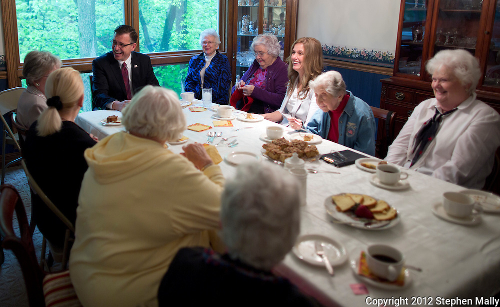 Rep. Bobby Schilling (R-Ill) and his wife, Christie, talk with the Old Glories at a home in Moline, Illinois on Monday, April 30, 2012. The Old Glories is a group of women over 70 years old.