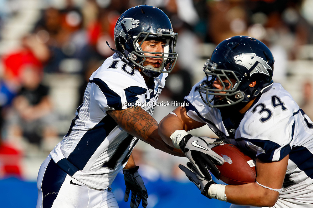 December 4, 2010; Ruston, LA, USA;  Nevada Wolf Pack quarterback Colin Kaepernick (10) hands off to running back Vai Taua (34) during the first half against the Louisiana Tech Bulldogs at Joe Aillet Stadium.  Mandatory Credit: Derick E. Hingle