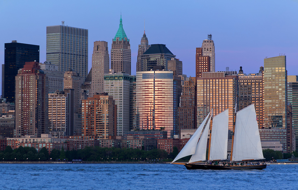 Sail boat heads north on the Hudson River, passing lower Manhattan, New York