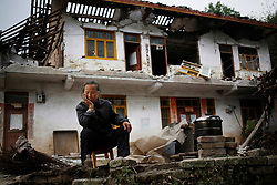 Chinese resident Ri Chenfu sits outside her home damaged by the earthquake in Lushan county of Ya'an, Sichuan Province, China, 21 April 2013. Her son was also missing after the quake. The Lushan Earthquake in Sichuan Province on 20 April 2013 resulted in 186 people dead, 21 missing, 11248 injured. About 1.72 million people were affected by the quake, while an initial estimate by the International Red Cross on Saturday put the number needing emergency shelter, water and food at 120,000. The China Earthquake Administration (CEA) recorded a magnitude 7.0 earthquake, while the US Geological Survey said it had measured 6.9.