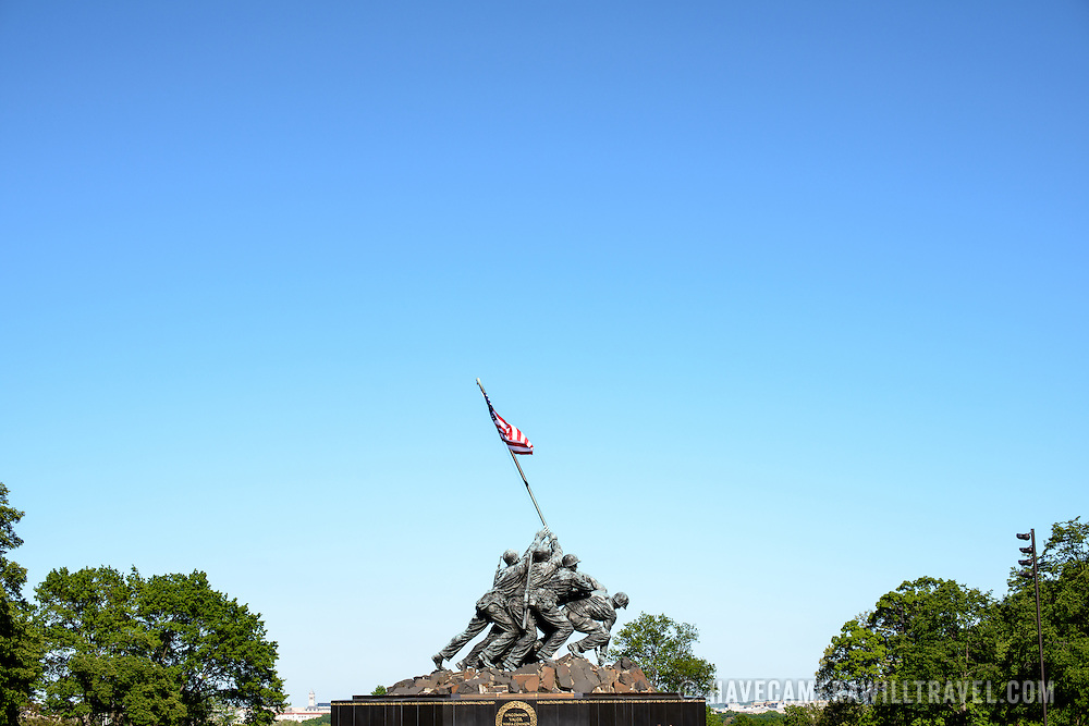 The statue against a blue sky at the Iwo Jima Memorial (formally the Marine Corps War Memorial) in Arlington, Virginia, next to Arlington National Cemetery. The monument was designed by Felix de Wledon and is based on an iconic Associated Press photo called the Raising the Flag on Iwo Jima by Joe Rosenthal. It was dedicated in 1954.