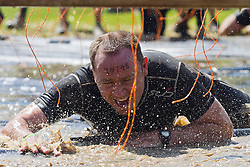 © Licensed to London News Pictures. 12/05/2012. Kettering, UK.A Tough Mudder competitor crawls along a wet floor underneath hanging electric wires. Thousands of people took part in Tough Mudder today (12/05) in the grounds of Boughton House, Northamptonshire. The 12 mile course which was designed by British special forces soldiers, consisted of 25 extreme obstacles including water, mud, electrocution, and high walls. The challenge is designed to test teamwork abilities as well as physical strength and stamina . Photo credit : James Gourley/LNP