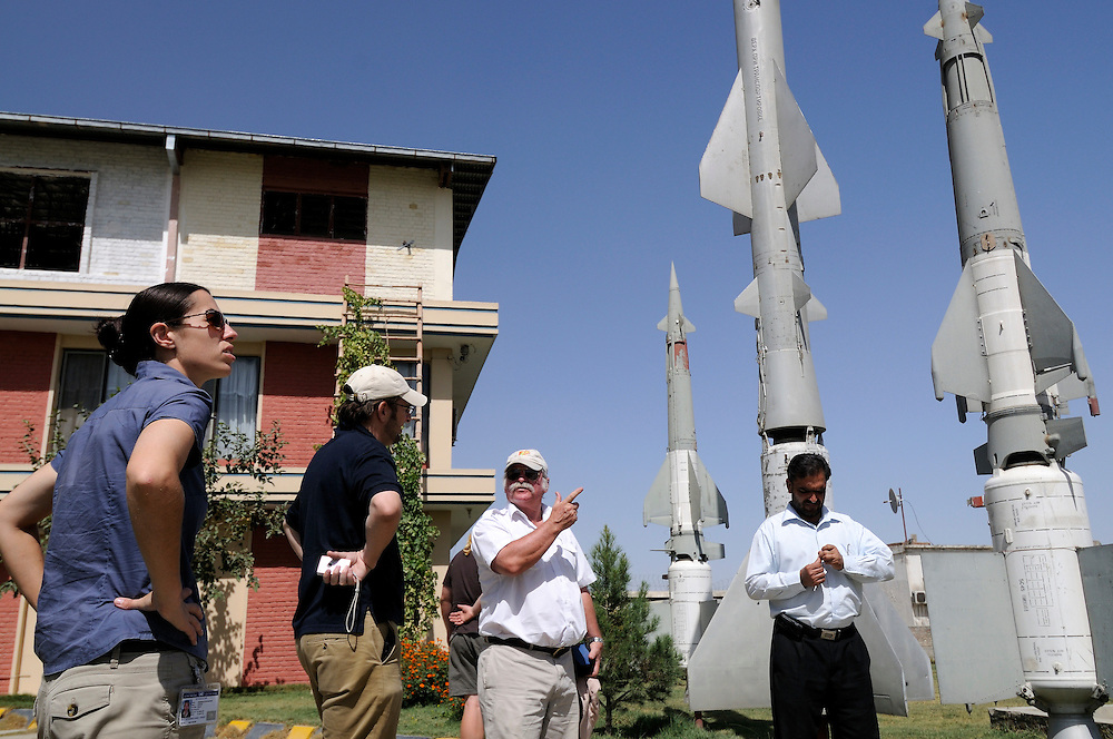 """Pilot, Danielle Aitchison, stands in front of a Russian Surface to Air Missles with UNHAS colleagues at the OMAR Landmine Museum in Kabul.  Danielle flies in Afghanistan for The United Nations Humanitarian Air Service (UNHAS).   Left to right:  Danielle, Pilot Chris Hood, and Base Manager Dave Findlay....When asked about flying in a war zone, she says,  """"I'm just a normal average female.  My job is maybe a little different to some, but I have the same feminine side as other women.  I don't have any trouble going back to New Zealand relating to people.  I'm just a regular chick.""""."""