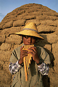 An Uru Murato boy plays the panpipes outside a traditional earthen house in Llapallapani Village, Lago Poopo, the Altiplano, Bolivia.