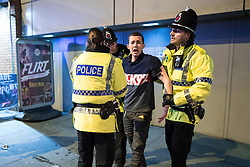 "© Licensed to London News Pictures . 24/12/2016 . Manchester , UK . Police detain a man on Withy Grove . Revellers out in Manchester City Centre overnight during 2016's second "" Mad Friday "" , named for historically being one of the busiest nights of the year for the emergency services in the UK . Photo credit : Joel Goodman/LNP"