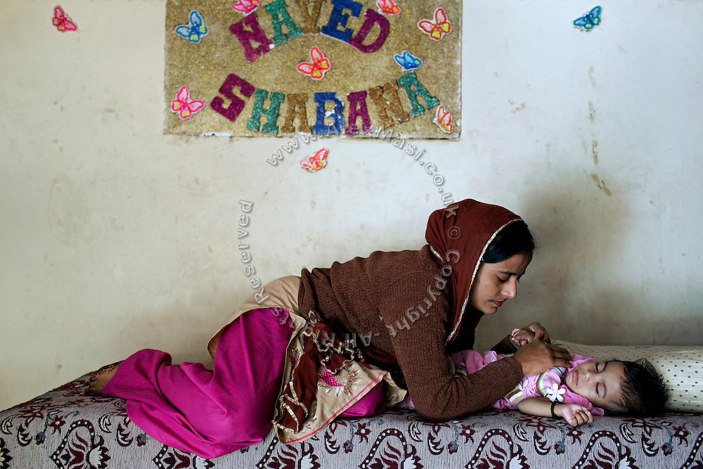 Shabana, 30, is looking after her young disabled daughter, Sufiya, one and a half years old, while lying on a bed inside their home in Kabar Kana, Bhopal, Madhya Pradesh, central India, site of the infamous 1984 gas tragedy. Sufiya is Shabana's first child and the family is now scared of considering further pregnancies. Sufiya suffers from a neurological disorder causing severe seizures and slow development. She is not able to eat or swallow food naturally, and is surviving only on water and milk. As a toddler, in 1984 Shabana survived the poisonous gas cloud that enveloped Bhopal, leaving everlasting consequences that today continue to consume people's lives.